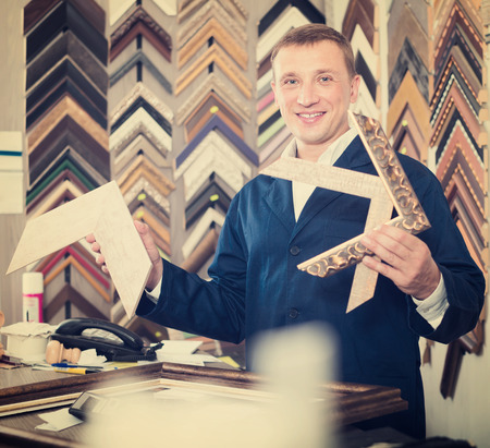 framer: professional man seller standing in picture framing studio with wooden details Stock Photo