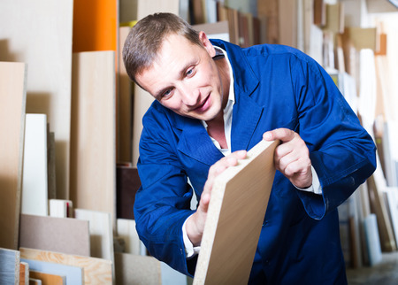 atelier: portrait of happy man in uniform choosing tight wooden bar in picture framing atelier Stock Photo