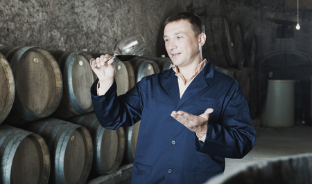 ageing process: Positive male in robe keeping ageing process of wine under control