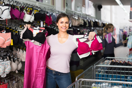 Cheerful young woman choosing sexy silky lingerie in shop Stock Photo