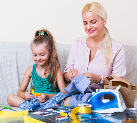 spanish home: Young mother teaching her little daughter to sew at home Stock Photo