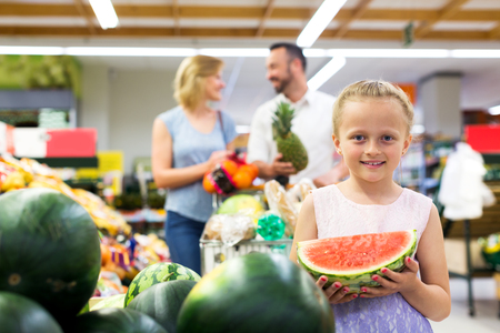 Portrait of positive girl holding slice of watermelon in grocery shop