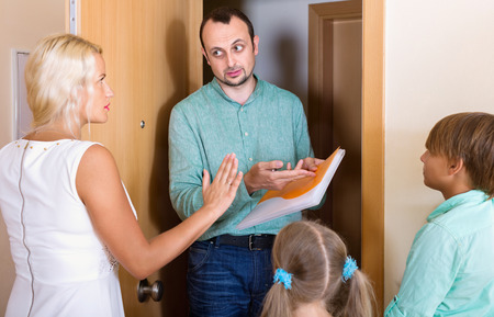 Serious collector trying to collect debt from  family with children standing on doorstep