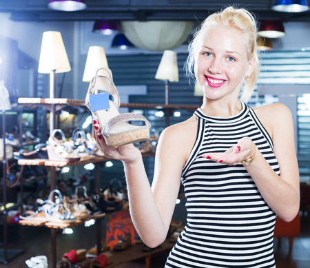 positive young female customer showing desired shoe in fashion  department