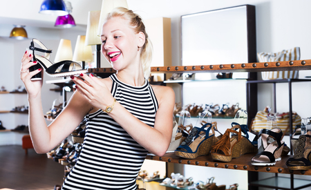 cheerful young female customer showing desired shoe in boutique