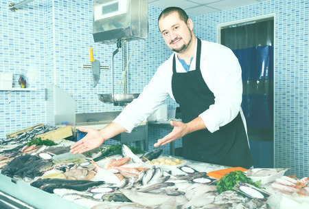 spaniard: man in black apron standing near fish counter and smiling