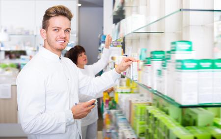 Handsome man pharmacist wearing white coat standing among shelves in drug store