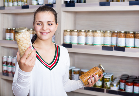 Smiling girl deciding on canned beans in the grocery shop