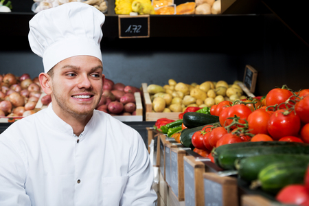 Smiling man cook deciding on best vegetables in grocery shop Stock Photo