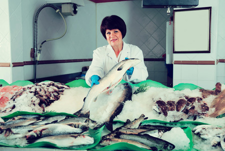 salmon fishery: Cheerful woman selling chilled fish and seafood in store