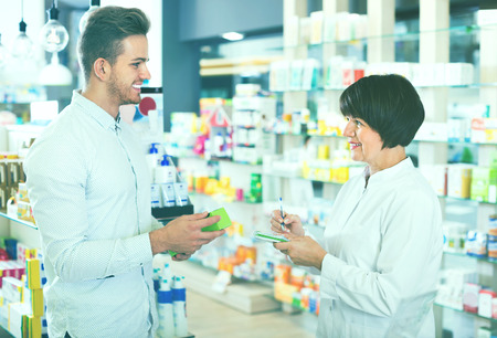 buying questions: Cheerful smiling  woman pharmacist in white coat helping customers to find item in drug store Stock Photo