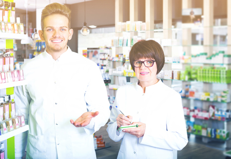 Happy team of pharmaceutist and technician working in chemist shop