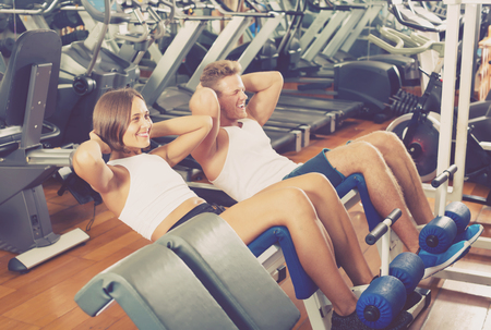 situp: Well trained young man and woman training abdominal muscles doing sit ups in gym