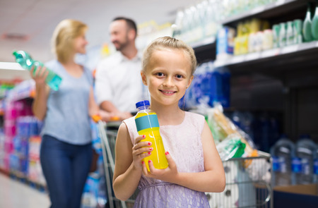 Portrait of smiling american girl holding plastic bottle with water in grocery shop