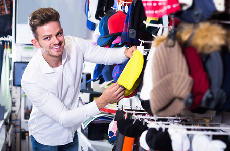 Young european male customer examining knit caps in sports store