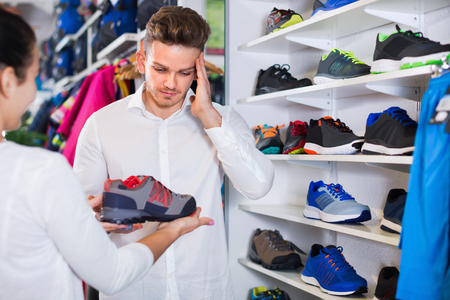 Smiling couple examining various sneakers in sports store