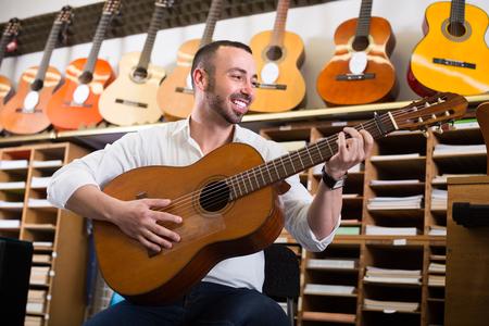 man in white shirt selecting classical guitar at studio