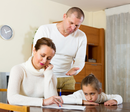 rapacity: poor family counting money to pay bills at home. Focus on woman Stock Photo