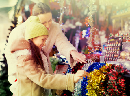 5s: Little girl and mom buying decorations for Xmas together. Focus on girl