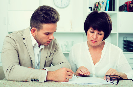 Smiling young man and mature woman sit at table and discuss legal aspects of paperwork Stock Photo