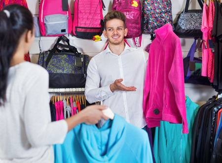 sleeveless hoodie: Young glad friendly  couple choosing new sportswear in sports store