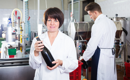 displaying: Smiling mature woman worker displaying wine bottle at sparkling wine factory Stock Photo