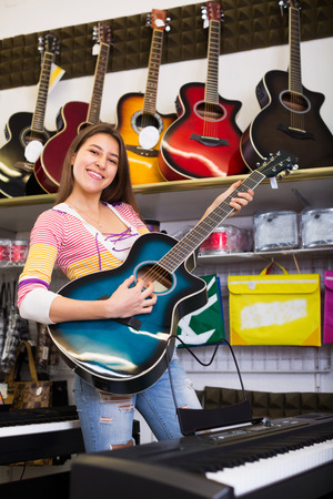 Happy young customer buying new guitar in store and smiling Stock Photo