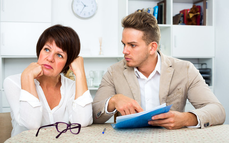 Mature mother was upset and has turned away from the son who suggests her to sign documents
