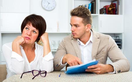 熟母は怒っていたし、文書に署名する彼女を示唆している息子からなっています。 写真素材