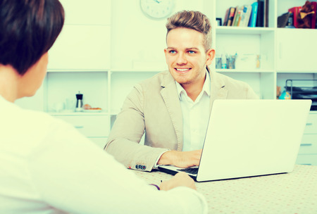 Young blond man and businesswoman communicate sitting at table Stock Photo