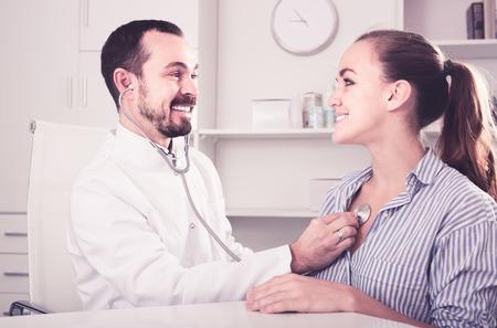 Sonriente mujer paciente con médico masculino en centro de medicina