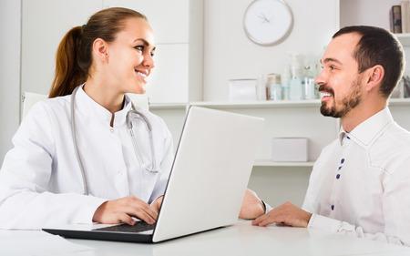 Consultoría visita paciente sonriente hombre con médico de la mujer en el hospital