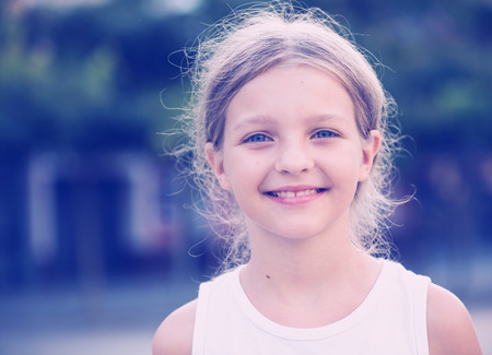 portrait of smiling girl standing outdoors on summer day Stock Photo