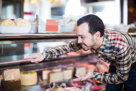 Young man choosing delicious cheese in supermarket Stock Photo