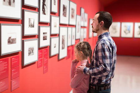 Father and girl exploring exhibition of photos in museum