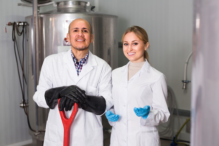 technologists: Two friendly smiling technologists in white coats working on beer brewery factory