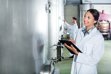 Young cheerful woman wearing coat taking notes in secondary fermenting section on wine factory