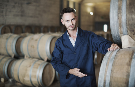 Portrait of young man working on secondary fermentation equipment in winery manufactory Stock Photo