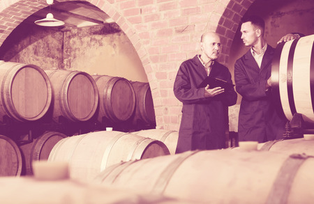 two thoughtful men professionals in uniforms taking notes in cellar with wine woods