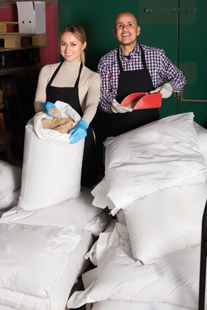 Glad man and woman holding gunnysacks with malt indoors