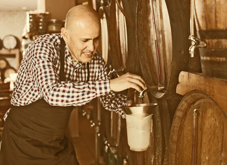 Positive mature seller pouring wine from wood barrel  in wine house