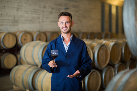 Young smiling man winery expert wearing coat holding glass of wine in large cellar