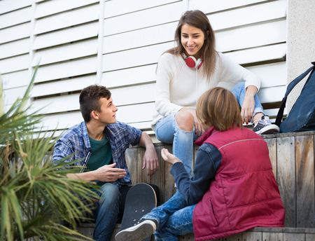 blabbing: Portrait of teenage males and caucasian girl talking in autumn day