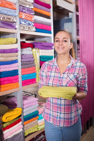 Girl customer deciding on the choice of towels in textile shop Stock Photo