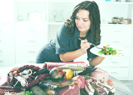 frenchwoman: Portrait of young slender woman chooses healthy food, but not sausages and smoked meat