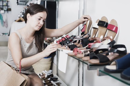 Portrait of cheerful woman customer selecting shoes in footgear center Stock Photo