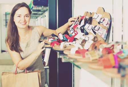 comprando zapatos: Portrait of happy woman customer selecting shoes in footgear center
