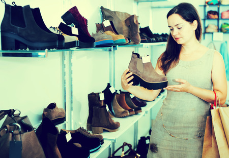 brogues: Smiling young brunette buying winter shoes in footwear shop