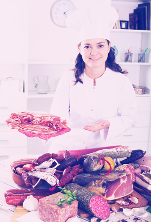 Cook girl costs near table with smoked products and sausage and holds in hand plate with jamon Stock Photo