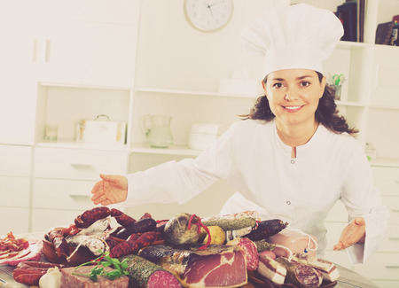 compounding: Young smiling positive girl cook costs near table on which sausages and smoked meat lie Stock Photo